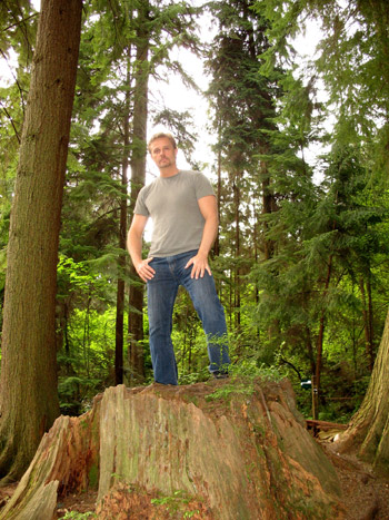 Andrew Standing on a Tree Stump in the Seven Sisters Area of Stanley Park in Vancouver, BC